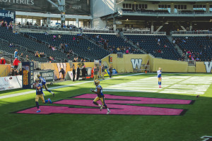 The Winnipeg Blue Bombers warm up for their Oct. 24 game against the Ottawa REDBLACKS during CFL Pink Week, part of a national campaign to raise awareness of women's cancers. THE PROJECTOR/Laura Hayward