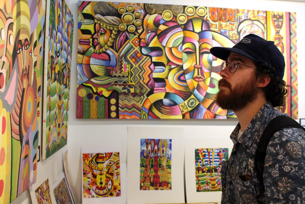Cameron Marlatt explores Gibril Bangura's art at the Nuit Noir event before performances began. THE PROJECTOR/ Jen Doerksen