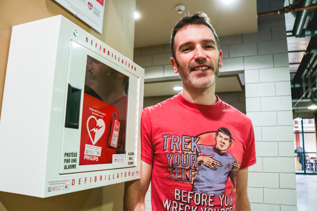 Kyle Geske stands by an AED at Red River College on Oct. 20. He said the CPR training he received through RRC once helped save his daughter's life. THE PROJECTOR/Connor Wielgosz