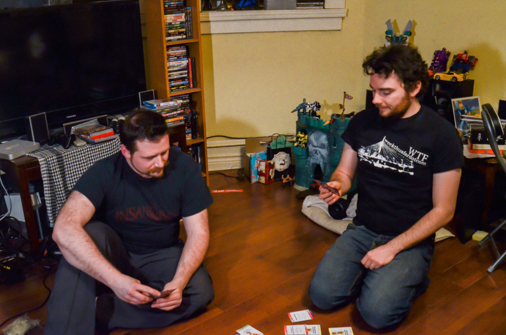 From left: Bart Rucinski and Will O'Donnell play Surplus of Popes, the card game they created. THE PROJECTOR/ Trenton Burton