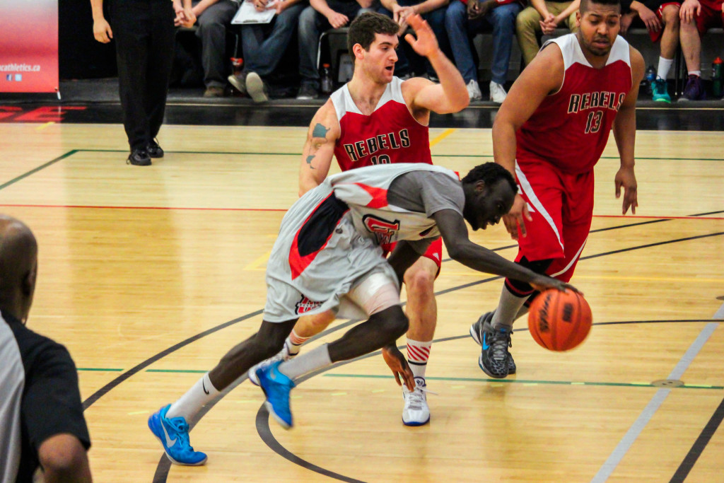 RRC's Ezekiel Lerner (centre) defends against Mohamed Alor of the Wesmen in the Rebels' 65-61 win over the University of Winnipeg College Wesmen on Saturday, Feb. 20. THE PROJECTOR/ Gus Gottfred
