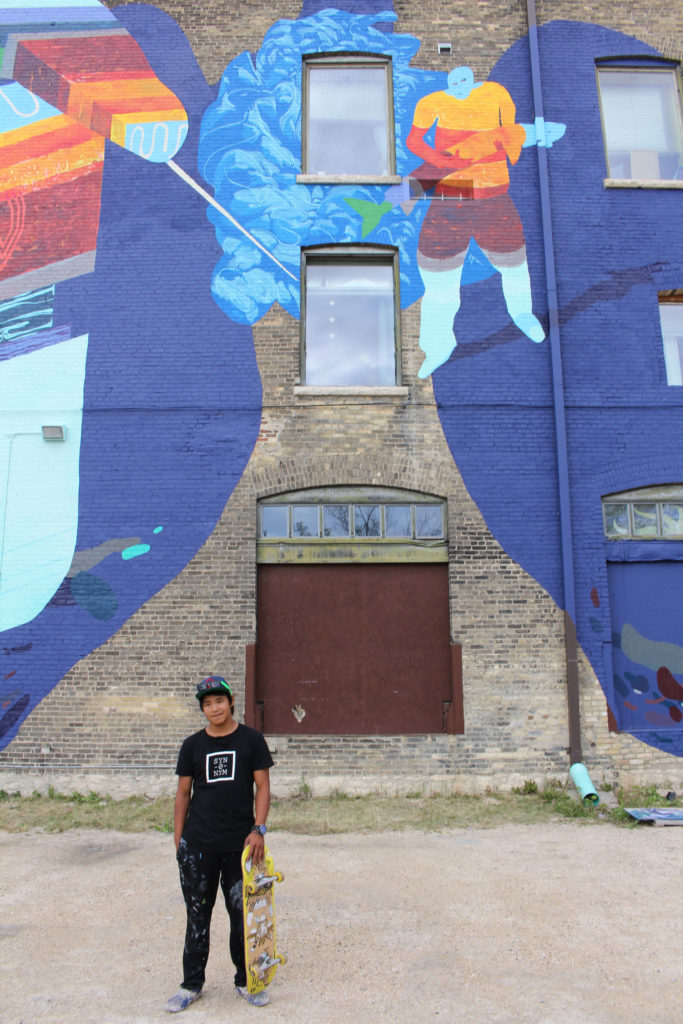 Par Josephee stands in front of the completed mural he helped design and incorporated a self-portrait into. THE PROJECTOR/ Jen Doerksen
