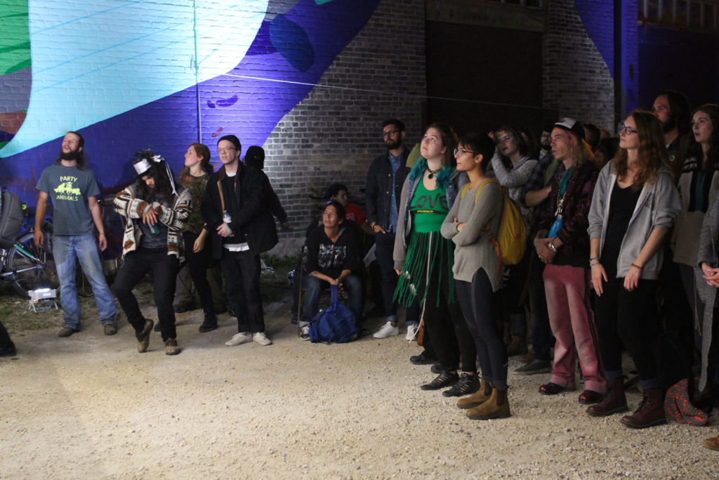 """Hundreds of people crowded under PA System and Parr Josephee's mural """"Aqua Lungs"""" to listen to Begonia belt it before the RTMF Bike Jam began. THE PROJECTOR/ Jen Doerksen"""