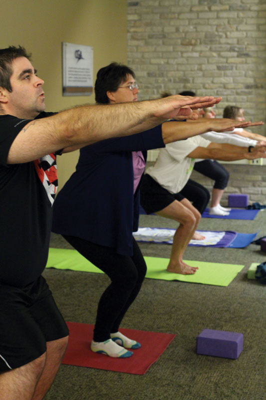 Participants of Caldwell's yoga class on October 18, 2016 do the chair pose. THE PROJECTOR/ Danica Taylor