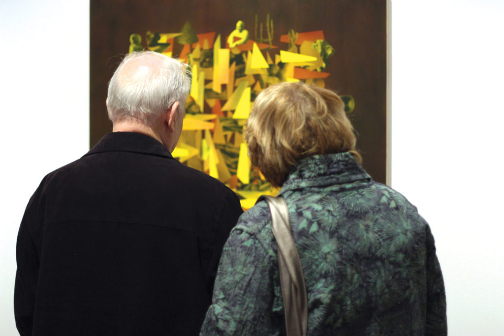 """A couple inspecting Simon Hughes' painting """"Golden Ghosts"""" during the exhibit. THE PROJECTOR/ Aiden Cloet"""