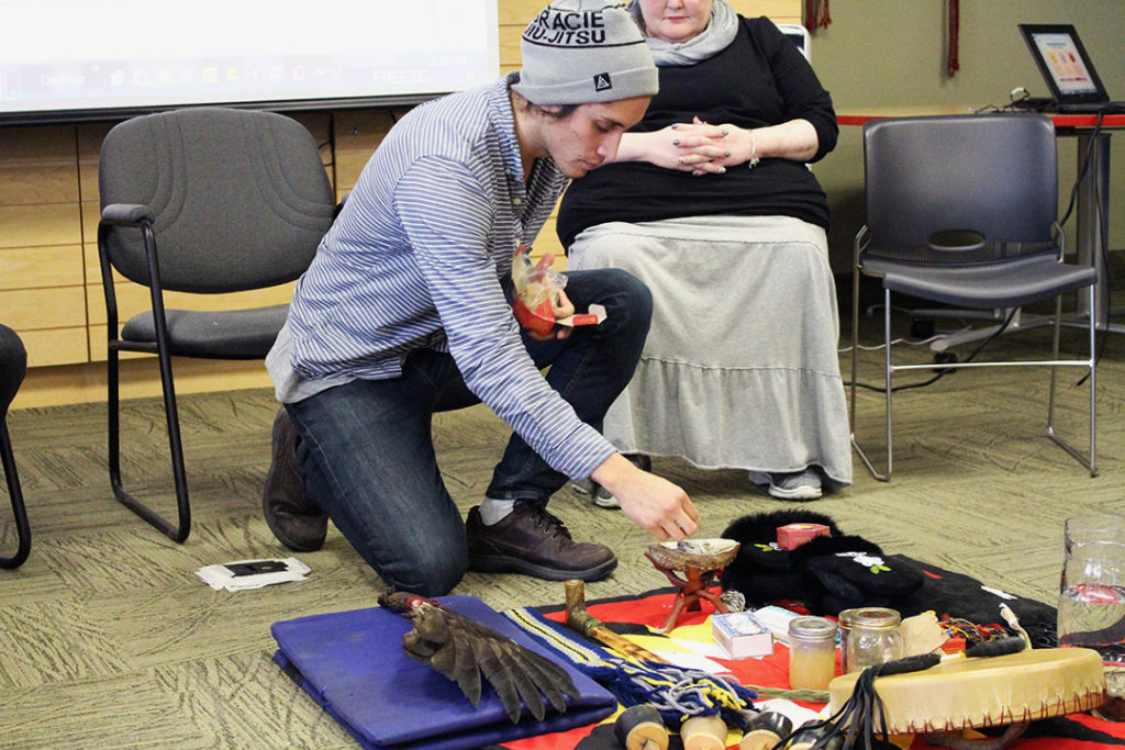 Kerry Norris-Woods, 24, lights sage from the sacred bundle to be used for spiritual healing in the seminar. THE PROJECTOR/ Joshua Houston